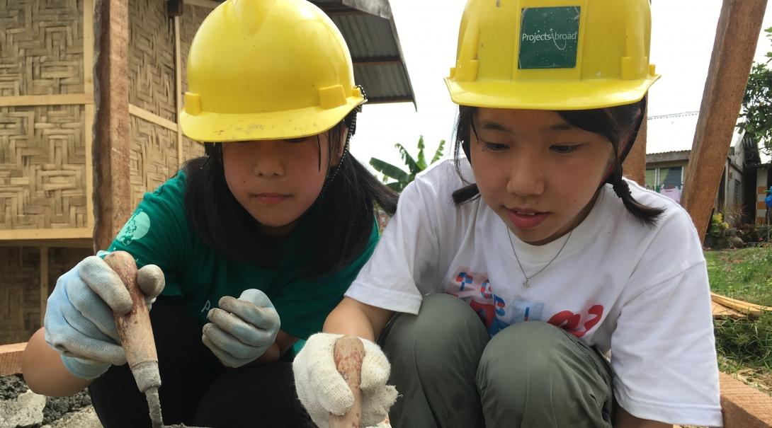 Two Projects Abroad volunteers building a house on one of our best volunteer abroad programmes